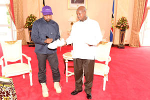 Rapper Kanye West (L) autographs a shoe as he meets Uganda's President Yoweri Museveni when he paid a courtesy call at State House, Entebbe, Uganda October 15, 2018. Presidential Press Unit/Handout via REUTERS ATTENTION EDITORS - THIS IMAGE WAS PROVIDED BY A THIRD PARTY.