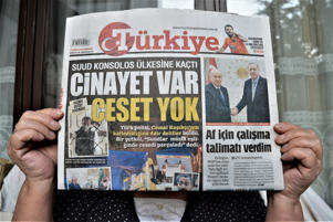 A woman shows Turkiye, a Turkish pro-government daily newspaper, as the daily runs a headline on its front page that reads 'There is a murder, but no body' in Ankara, Turkey on October 17, 2018. Saudi Arabian journalist Jamal Khashoggi went missing after entering his country's consulate in Istanbul on October 2. (Photo by Altan Gocher/NurPhoto via Getty Images)