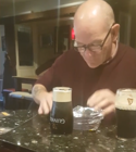 Pub-goer performs trick with a pint of Guinness and packet of crisps