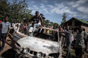 Congolese men look on at a car which has hit by a mortar, after an alleged attack by the Allied Democratic Forces(ADF) rebels, killing one women and kidnapping four children and one man  in Beni on November 11, 2018. (Photo by John WESSELS / AFP)        (Photo credit should read JOHN WESSELS/AFP/Getty Images)