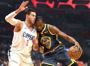 Golden State Warriors forward Kevin Durant (35) collides with Los Angeles Clippers forward Danilo Gallinari (8) on a drive to the basket during the first quarter on Nov. 12 in Los Angeles.