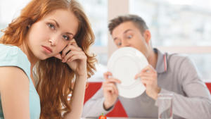 a man and a woman eating a donut: That first date can be stressful enough — imagine if an awkward money situation arises on top of all the other things you're worried could go wrong. Even a great date can go downhill quickly if someone makes a financial faux pas. The key is to be prepared for any scenario so you can respond appropriately. Here are 10 awkward money moments that can happen — and dating advice on how to handle them with grace and ease. Click through to see how to handle awkward money situations without breaking a sweat.