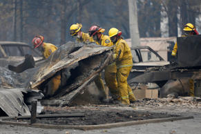 Cal Fire firefighters comb through a house destroyed by the Camp Fire in Paradise, California, U.S., November 13, 2018.  REUTERS/Terray Sylvester