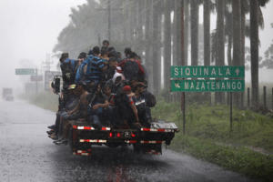 SIQUINALA, GUATEMALA - OCTOBER 18:  People in a migrant caravan make their way through Guatemala towards the border with Mexico on October 18, 2018 in Siquinala, Guatemala. The immigrants were part of a migrant caravan of thousands of Central Americans, most from Honduras, hoping to eventually reach the United States. U.S. President Donald Trump has threatened to cancel the recent trade deal with Mexico and withhold aid to Central American countries if the caravan isn't stopped before reaching the U.S.  (Photo by John Moore/Getty Images)