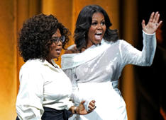 Former US first lady Michelle Obama (R) and Oprah Winfrey attend the opening of Obama's multi-city book tour at the United Center in Chicago, November 13, 2018. - Former US first lady Michelle Obama's book, 'Becoming,' hits stores on Tuesday. Obama, 54, will head out on a multi-city arena tour to promote the memoir, with celebrity friends like Oprah Winfrey and Reese Witherspoon tapped to moderate the events. (Photo by JIM YOUNG / AFP)        (Photo credit should read JIM YOUNG/AFP/Getty Images)