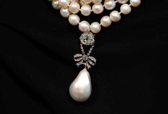 Slide 1 of 17: Queen Marie Antoinette's Pearl displayed at Sotheby's in London, Friday, Oct. 19, 2018. The Pearl is estimated to fetch 1 million to 2 million USD. Jewels once owned by the last Queen of France Marie Antoinette will be going up for auction this autumn. And before the auction, the collection is making stops on an international tour where members of the public can view and even try on the royal pieces. (AP Photo/Frank Augstein)