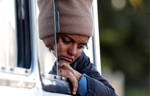 A migrant woman, a part of a caravan of thousands traveling from Central America en route to the United States, sit in a bus while the bus stop for them to get food and water from a store on a highway in Culiacan, Mexico November 15, 2018.