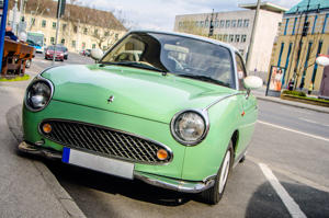 Kecskemet, Hungary - March 30, 2016: A green colored Nissan Figaro parked on a street in Kecskemet, Hungary. The Nissan Figaro is a small retro car manufactured by Nissan only in 1991. The car was originally sold only in Japan with only 20,000 models being produced.