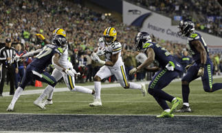 Green Bay Packers running back Aaron Jones, center, runs for a touchdown against the Seattle Seahawks during the first half of an NFL football game, Thursday, Nov. 15, 2018, in Seattle. (AP Photo/Stephen Brashear)