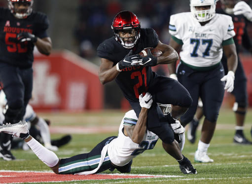 Slide 2 of 75: HOUSTON, TX - NOVEMBER 15:  Patrick Carr #21 of the Houston Cougars runs the ball defended by Thakarius Keyes #26 of the Tulane Green Wave in the second quarter at TDECU Stadium on November 15, 2018 in Houston, Texas.  (Photo by Tim Warner/Getty Images)