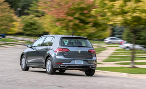 a man riding on the back of a car going down the road: Despite a Smaller Engine, the 2019 Golf Is No Slower and No Worse Off