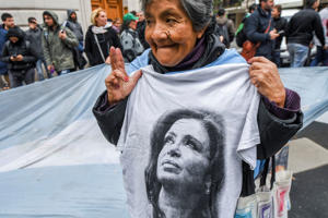 A supporter of former Argentine President and current senator Cristina Fernandez de Kirchner demonstrates as Argentina's Federal Police raids one of her properties as part of the so-called corruption notebooks case, in Recoleta neighbourhood, Buenos Aires, on August 23, 2018. - The move came after judge Claudio Bonadio successfully petitioned the Senate on Wednesday to partially lift Kirchner's parliamentary immunity so her three residences could be searched for evidence of multi-million dollar bribes paid by businessmen in exchange for public works contracts during her administration. As a senator, Kirchner enjoys congressional immunity from imprisonment, though not prosecution. (Photo by EITAN ABRAMOVICH / AFP)        (Photo credit should read EITAN ABRAMOVICH/AFP/Getty Images)