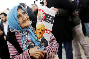 A woman holding a picture of Saudi journalist Jamal Khashoggi attends a symbolic funeral prayer for Khashoggi at the courtyard of Fatih mosque in Istanbul, Turkey Nov. 16.