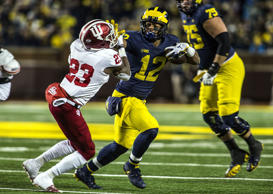 Michigan's Chris Evans (12) holds his arm out to keep away Indiana's Jaylin Williams, in Ann Arbor, Mich., on Nov. 17. Michigan won 31-20.