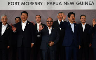 (L to R-front row) Chile's President Sebastian Pinera, China's President Xi Jinping, Papua New Guinea's Prime Minister Peter O'Neill and Japan's Prime Minister Shinzo Abe wave with (back row L to R) Philippine President Rodrigo Duterte, Russia's Prime Minister Dmitry Medvedev, Singapore's Prime Minister Lee Hsien Loong and South Korea's President Moon Jae-in as they pose for a 'family photo' during the Asia-Pacific Economic Cooperation (APEC) Summit in Port Moresby on November 18, 2018. (Photo by SAEED KHAN / AFP)        (Photo credit should read SAEED KHAN/AFP/Getty Images)