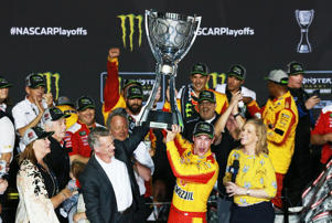HOMESTEAD, FL - NOVEMBER 18:  Joey Logano, driver of the #22 Shell Pennzoil Ford, celebrates with the trophy in victory lane after winning the Monster Energy NASCAR Cup Series Ford EcoBoost 400 and the Monster Energy NASCAR Cup Series Championship at Homestead-Miami Speedway on November 18, 2018 in Homestead, Florida.  (Photo by Sean Gardner/Getty Images)