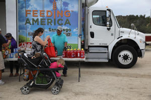 JACAMBA HOT SPRINGS, CA - SEPTEMBER 26:  Residents receive free food at mobile food pantry near the U.S.-Mexico border on September 26, 2016 in Jacamba Hot Springs, California. The Feeding America truck delivers to the border town's needy residents twice a month.  (Photo by John Moore/Getty Images)