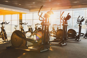 Modern gym interior with equipment. Fitness club with training exercise elliptical trainers, backlight in evening sunlight.