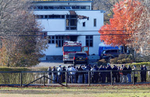 Authorities gather Wednesday, Nov. 21, 2018, in Colts Neck,N.J., to investigate the aftermath of fatal fire that killed two children and two adults. Authorities say two adults and two children were found dead the day before at the scene of a burning mansion near the New Jersey shore.  (AP Photo/Noah K. Murray)