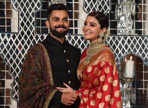 Indian cricketer Virat Kohli (L) and Bollywood actress Anushka Sharma, who were recently married in Italy, pose during a reception in New Delhi on December 21, 2017. The wedding in Tuscany on December 11 ended weeks of speculation in the gossip pages of India's newspapers and on the airwaves of the country's excitable 24-hour news channels that the couple had recently got engaged. Kohli and Sharma, dubbed 'Virushka' by local media, have generated the same sort of excitement and coverage in India as Britain's Prince Harry and fiance Meghan Markle have in the West.  / AFP PHOTO / PRAKASH SINGH        (Photo credit should read PRAKASH SINGH/AFP/Getty Images)