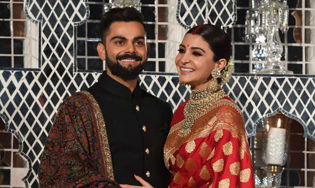 Slide 1 of 20: Indian cricketer Virat Kohli (L) and Bollywood actress Anushka Sharma, who were recently married in Italy, pose during a reception in New Delhi on December 21, 2017. The wedding in Tuscany on December 11 ended weeks of speculation in the gossip pages of India's newspapers and on the airwaves of the country's excitable 24-hour news channels that the couple had recently got engaged. Kohli and Sharma, dubbed 'Virushka' by local media, have generated the same sort of excitement and coverage in India as Britain's Prince Harry and fiance Meghan Markle have in the West.  / AFP PHOTO / PRAKASH SINGH        (Photo credit should read PRAKASH SINGH/AFP/Getty Images)