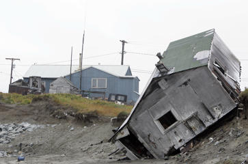 A home destroyed by beach erosion tips over 27 September 2006 in the the Alaskan village of Shishmaref. The village, home of Inupiat Eskimos, is located some 600 miles (965kms) northwest of Anchorage but just 110 miles (177kms) from the east coast of Russia. Shishmaref, on an island reachable only by air and inhabited for 4,000 years, is facing evacuation because of global warming. Temperatures that have risen 15F (4.4C) over the last 30 years are causing a reduction in sea ice, thawing of permafrost along the coast, making the shoreline vulnerable to erosion. The census of 2000 reported there were 562 people, 142 households, and 110 families residing in the village all facing evacuation and the loss of their traditional life. AFP PHOTO/GABRIEL BOUYS     =MORE PHOTOS IN IMAGE FORUM= / AFP PHOTO / Gabriel BOUYS        (Photo credit should read GABRIEL BOUYS/AFP/Getty Images)