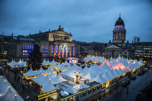 The Gendarmenmarkt Christmas market glows with light in Berlin, Germany, 27 November 2017. The Christmas market in front of the the Konzerthaus in Berlin opened its doors during rainy weather and cool temperatures. Photo: Paul Zinken/dpa (Photo by Paul Zinken/picture alliance via Getty Images)