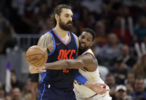 Oklahoma City Thunder's Steven Adams, left, New Zealand, passes against Cleveland Cavaliers' Tristan Thompson in the first half of an NBA basketball game, Wednesday, Nov. 7, 2018, in Cleveland.