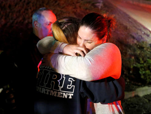 Slide 1 of 39: People comfort each other after a mass shooting at a bar in Thousand Oaks, California, U.S. November 8, 2018. REUTERS/Ringo Chiu     TPX IMAGES OF THE DAY - RC16E96E12C0