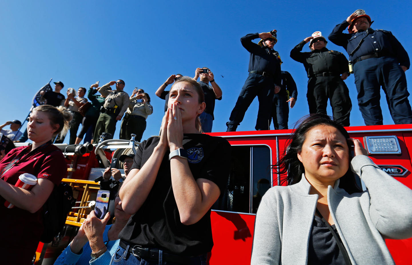 Madison Fuller (middle) of Thousand Oaks reacts as she watches from an overpass as a procession for the body of Sergeant Ron Helus, who died in a shooting incident at a Thousand Oaks bar, drives down Ventura HIghway 101 in Thousand Oaks, California, U.S. November 8, 2018.