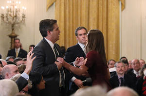 A White House intern reaches for and tries to take away the microphone held by CNN correspondent Jim Acosta as he questions U.S. President Donald Trump during a news conference at the White House in Washington, U.S., November 7, 2018. Picture taken November 7, 2018. REUTERS/Jonathan Ernst  (Picture 10 in a sequence of 15)