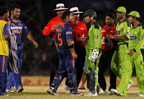 India's Gautam Gambhir (C, in blue) and Pakistan's wicketkeeper Kamran Akmal (wearing helmet) argue during the Asia Cup one-day international cricket tournament in Dambulla June 19, 2010.