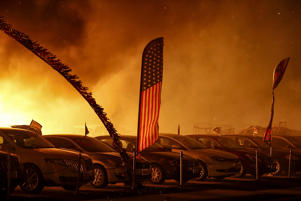 An American flag is seen at an engulfed car dealership during the Camp Fire in Paradise, California, U.S. November 8, 2018.