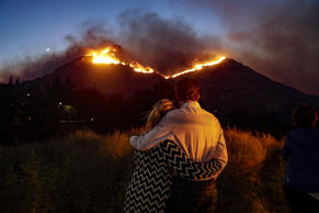 Roger Bloxberg, right, and his wife Anne hug as they watch a wildfire on a hill top near their home Friday, Nov. 9, 2018, in West Hills, Calif.