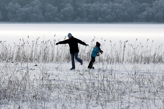 Slide 1 of 38: NOTE ALTERNATE CROP A couple skate on a frozen Lake of Menteith on Christmas Day. (Photo by Andrew Milligan/PA Images via Getty Images)