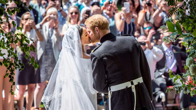 Slide 1 of 75: Meghan Markle and Prince Harry kiss on the steps of St George's Chapel