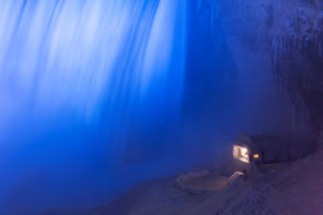A building covered in ice sits at the base of the Horseshoe Falls in Niagara Falls