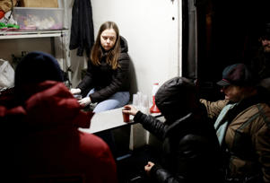 People queue near a van of 'Nochlezhka' charity organization as volunteers distribute meals for the homeless in St. Petersburg, Russia December 5, 2018. Picture taken December 5, 2018. REUTERS/Anton Vaganov