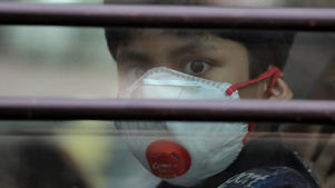 A schoolboy wearing a protective mask in Ghaziabad on the outskirts of Delhi [Anushree Fadnavis/Reuters]