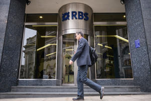 LONDON, ENGLAND - OCTOBER 08: A commuter walks past a branch of RBS bank, a decade after the British Government paid billions of pounds to support the UK banking sector during the 2008 financial crash, on October 08, 2018 in London, England. The Royal Bank of Scotland is still 62% owned by the British taxpayer, down from 70% in 2008, after a £20billion payment to prevent the collapse of the lender as the crisis deepened.  (Photo by Leon Neal/Getty Images)