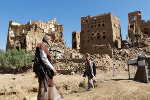 People walk past ruins of houses during the conflict in the northwestern city of Saada, Yemen, November 22, 2018. Picture taken November 22, 2018. REUTERS/Naif Rahma