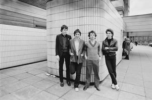 Buzzcocks (from left: drummer John Maher, guitarist Steve Diggle, guitarist and singer Pete Shelley and bassist Steve Garvey), British punk band, pose for a group portrait standing by a tiled wall in a shopping precinct, in May 1978. (Photo by Fin Costello/Redferns/Getty Images)