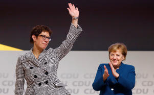 Annegret Kramp-Karrenbauer waves next to German Chancellor Angela Merkel after being elected as the party leader during the Christian Democratic Union (CDU) party congress in Hamburg, Germany, December 7, 2018. REUTERS/Kai Pfaffenbach