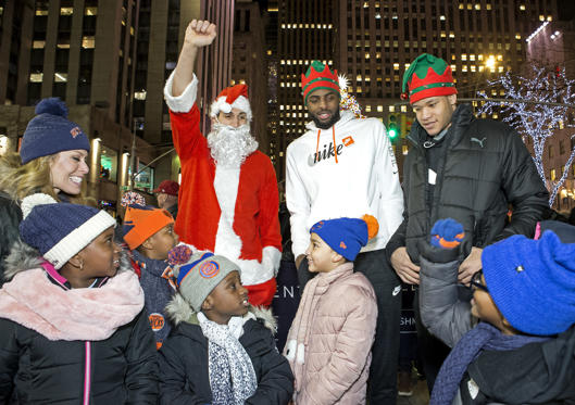 Slide 1 of 77: Enes Kanter #00, Kevin Knox #20 and Mitchell Robinson #26 of the New York Knicks with tv personality Jill Martin, surprise children from the Garden of Dreams Foundation at the Rockefeller Center Christmas tree in New York City on December 7, 2018. NOTE TO USER: User expressly acknowledges and agrees that, by downloading and or using this photograph, user is consenting to the terms and conditions of Getty Images License Agreement. Mandatory Copyright Notice: Copyright 2018 NBAE (Photo by Michelle Farsi/NBAE via Getty Images)
