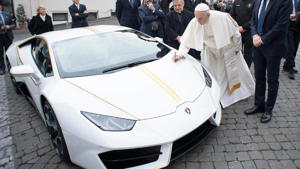 a group of people standing in front of a car: Pope Francis Signed Lamborghini Huracan