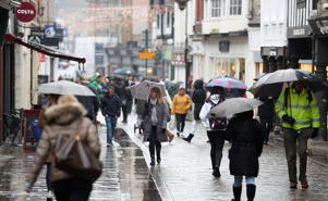Shoppers brave the rain as they make their way down the High Street in Winchester, Hampshire. (Photo by Andrew Matthews/PA Images via Getty Images)