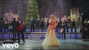 "a group of people on a stage: Order Kelly's Christmas record, ""Wrapped in Red"" here: http://smarturl.it/WrappedinRed?iqid=uttvid  Kelly Clarkson's Cautionary Christmas Music Tale Dec. 11 at 10 p.m (ET/PT) on NBC  Music video by Kelly Clarkson performing Underneath the Tree. (C) 2013 RCA Records, a division of Sony Music Entertainment"