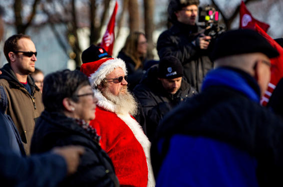 Slide 1 of 56: A man dressed as Santa Claus listens as Unifor launches its #SaveOshawaGM campaign by unveiling its Tree of Hope in Memorial Park in Oshawa, Ontario, Canada, December 13, 2018.