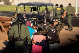 TOPSHOT - Central American migrants, travelling in a caravan, are taken into custody by US border patrol officers after crossing the Mexico-US border fence to San Diego County, as seen from Playas de Tijuana, Baja California state, Mexico on December 13, 2018. (Photo by Guillermo Arias / AFP)        (Photo credit should read GUILLERMO ARIAS/AFP/Getty Images)