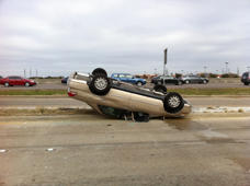 Car fallen upside-down on road in accident, Houston.